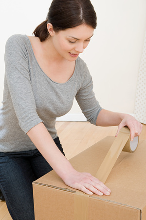 Woman Taping Up Box LANG_EVOIMAGES