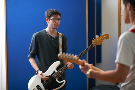 Young male college students playing guitars in recording studio LANG_EVOIMAGES