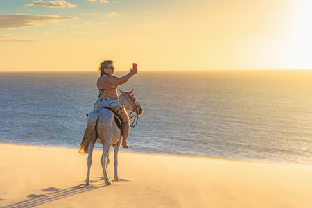 Woman riding horse on beach, taking picture of view using smartphone, Jericoacoara, Ceara, Brazil, South America