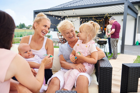 Three generation women with children on laps at family lunch on patio