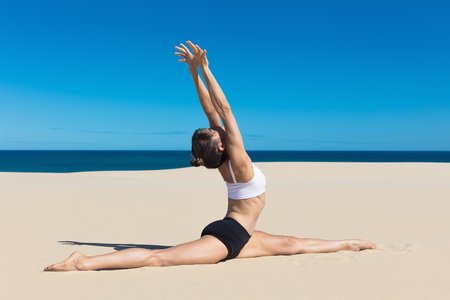 Side view of woman on beach doing the splits, arms raised in yoga position LANG_EVOIMAGES
