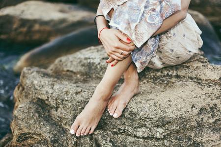 Vista de cintura abajo de una mujer joven sentada descalza sobre roca costera, Odessa, Ucrania