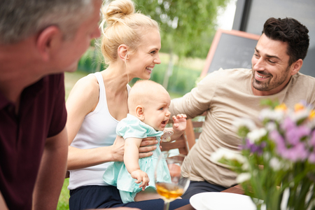 Couple with baby daughter at family lunch on patio LANG_EVOIMAGES