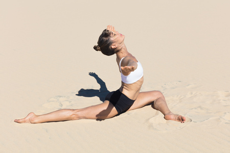 Side view of woman on beach doing the splits, arms open in yoga position LANG_EVOIMAGES
