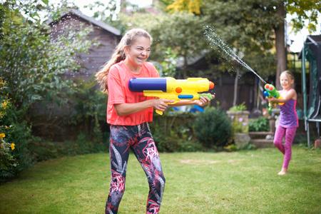 Teenage girl and her sister having water gun fight in garden