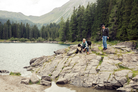 Couple with dogs hiking by lake, Tirol, Steiermark, Austria, Europe LANG_EVOIMAGES