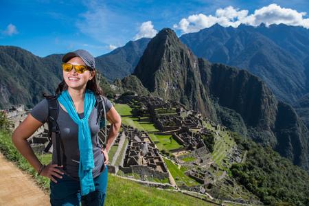 Woman at Inca ruins looking at camera smiling, Machu Picchu, Cusco, Peru, South America