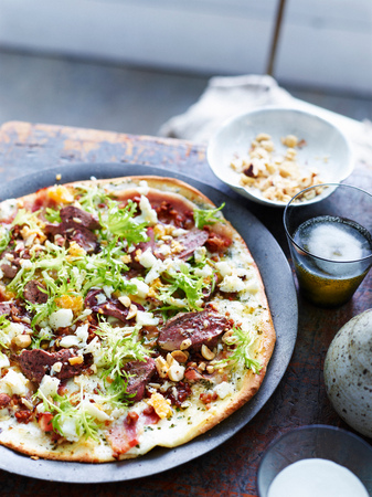 Frisee lardon pizza on plate, close-up