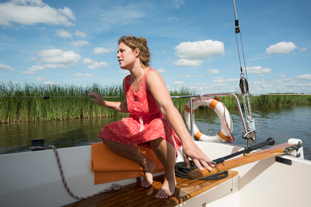 Woman on boat in the Frisian lake district in vintage dress, Sneek, Friesland, Netherlands