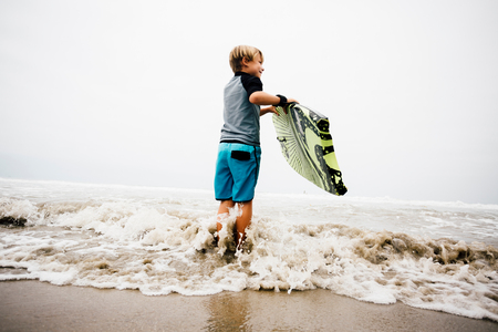 Young boy standing in sea, holding bodyboard LANG_EVOIMAGES