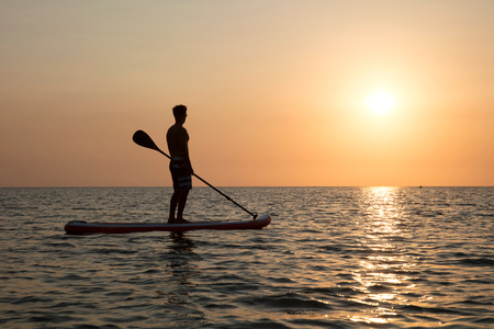 Man on paddleboard at sunset, Kilindoni, Pwani, Tanzania, Africa LANG_EVOIMAGES
