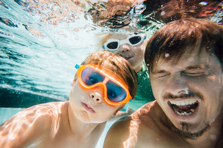 Portrait of father and sons, under water, underwater view