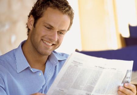 Man reading newspaper LANG_EVOIMAGES
