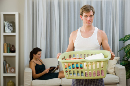 A man doing laundry whilst a woman relaxes