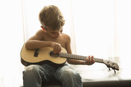 Niño tocando la guitarra en casa