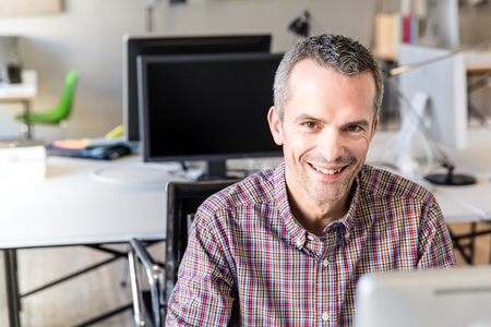 Mature man in office looking at camera smiling LANG_EVOIMAGES