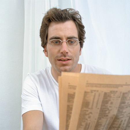Man reads financial pages LANG_EVOIMAGES