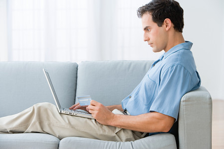 Man using a laptop computer at home LANG_EVOIMAGES
