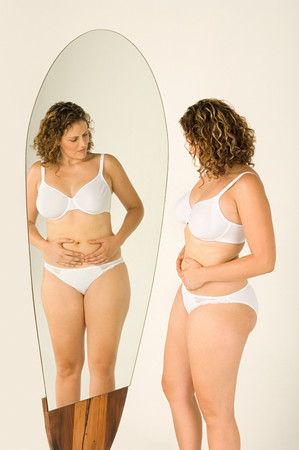 Woman looking at stomach in the mirror LANG_EVOIMAGES