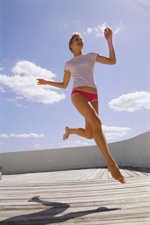 Woman running on decking LANG_EVOIMAGES
