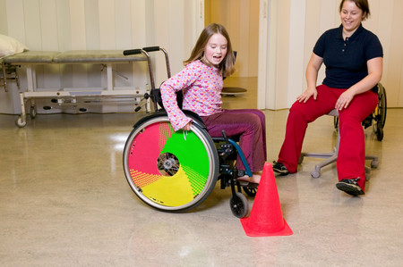 Girl learning to use wheelchair