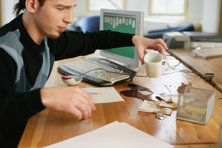 Man with coffee spilt on his desk