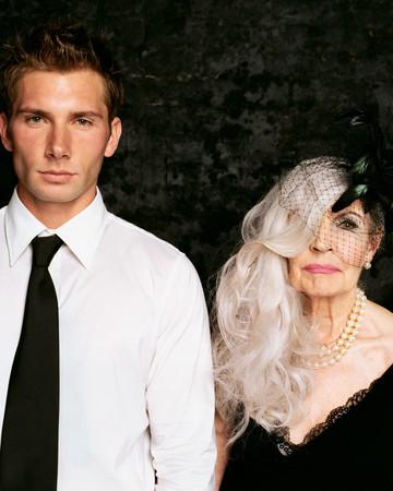 Young man and senior woman looking at camera