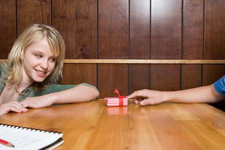 Teenage boy giving girl a present LANG_EVOIMAGES