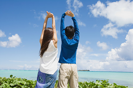 Couple with arms raised by ocean LANG_EVOIMAGES