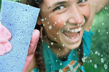 Girl cleaning glass with sponge