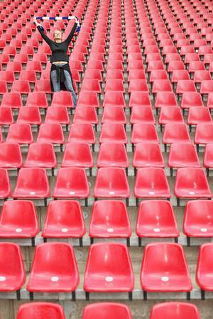 Female football fan alone in stadium