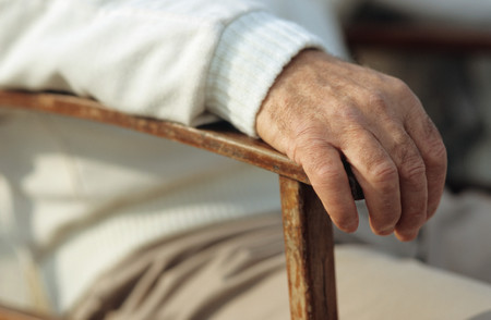 Mans hand resting on chair LANG_EVOIMAGES