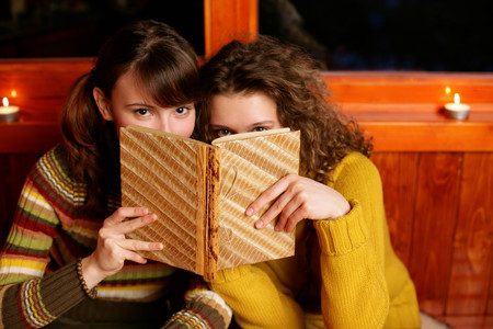 Two women peeking over a book LANG_EVOIMAGES