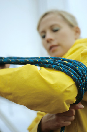 Woman winding rope around her arm LANG_EVOIMAGES