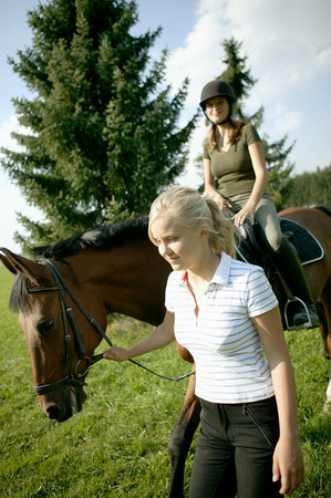 Woman leading horse and rider