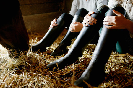Two people wearing riding boots