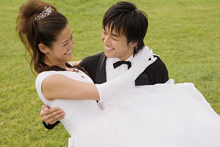 Groom carrying bride LANG_EVOIMAGES