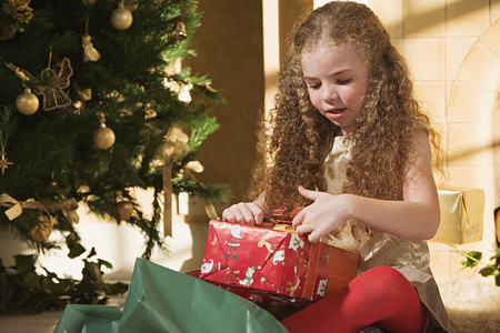 Girl opening christmas presents LANG_EVOIMAGES