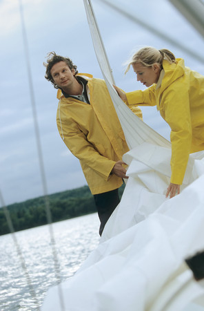 Couple taking down sail on boat