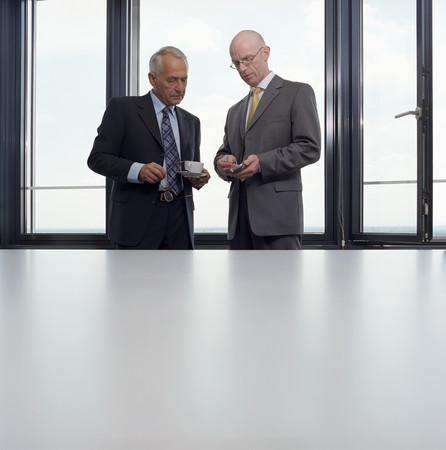 Businessmen looking at palmtop