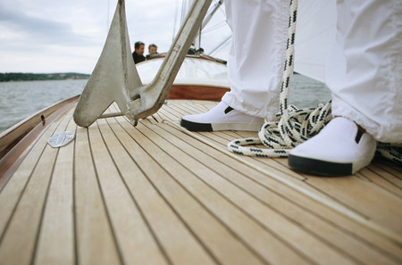 Close-up of feet and anchor on deck of boat LANG_EVOIMAGES