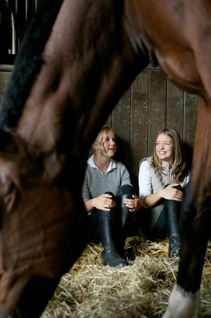 A horse in front of two women in a stable