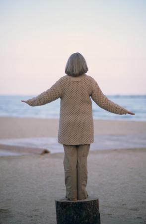 Senior woman balancing on a log