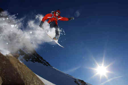 Snowboarder jumping off a rock LANG_EVOIMAGES