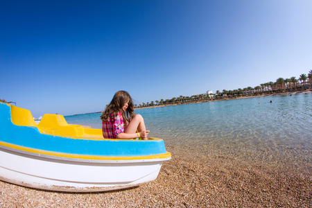 Girl sitting in a beached pedalo looking over her shoulder