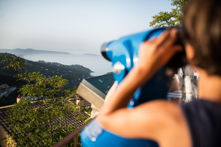 Over shoulder view of boy looking through coin operated binoculars at misty coastline landscape, Begur, Catalonia, Spain