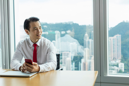 Business man at desk with smartphone looking away smiling LANG_EVOIMAGES