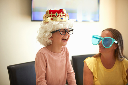 Mother and daughter playing dress up, wearing funny hats and glasses, laughing