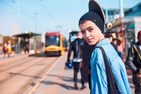 Portrait of cool young female skateboarder in beanie hat at tram station LANG_EVOIMAGES