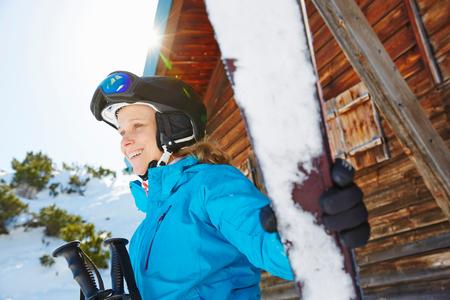 Woman in front of ski lodge, holding skis LANG_EVOIMAGES
